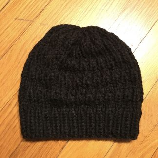 A black knit beanie with a striped and checkered texture